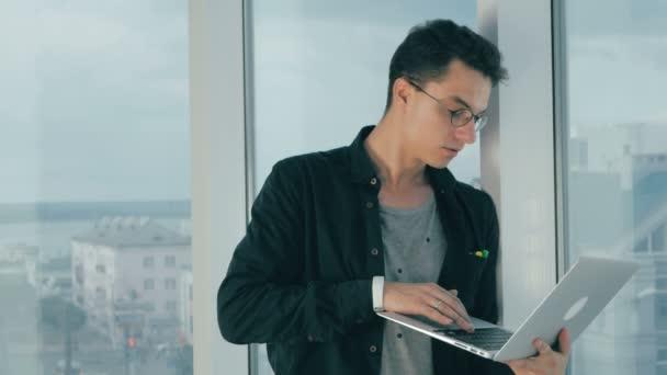 Mladá móda muži, kteří pracují na notebooku v moderní světlé kanceláře