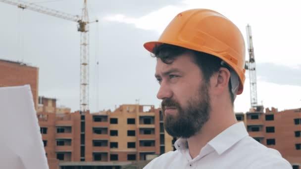 Profesionální architekt při pohledu na plány na staveniště.