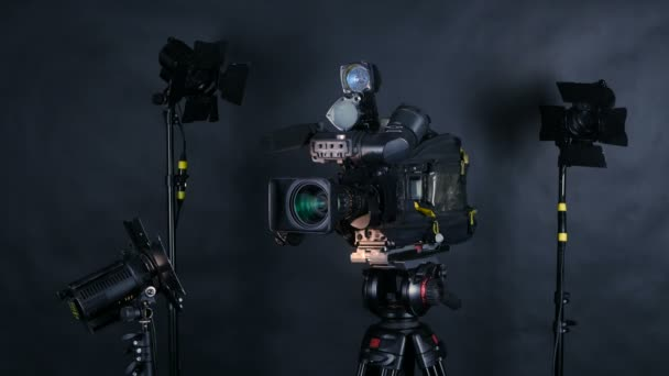 Professional digital video camera, camcoder isolated on black background in tv srudio.