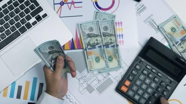 Úspěšný muž v počítání bankovek peníze se nám hodila dolarů na kalkulačce. Nad zobrazením. Grafy, laptop, kalkulačka na stůl