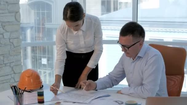 Ingenieure und Architekten diskutieren den Bauplan in modernem hellen Büro.