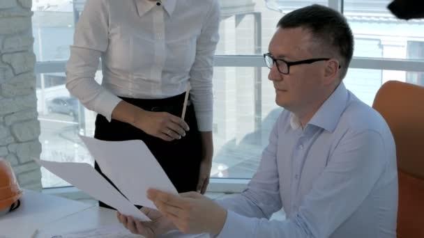 Csoport mérnökök és építészek megvitassák a blueprint a modern, világos irodai.