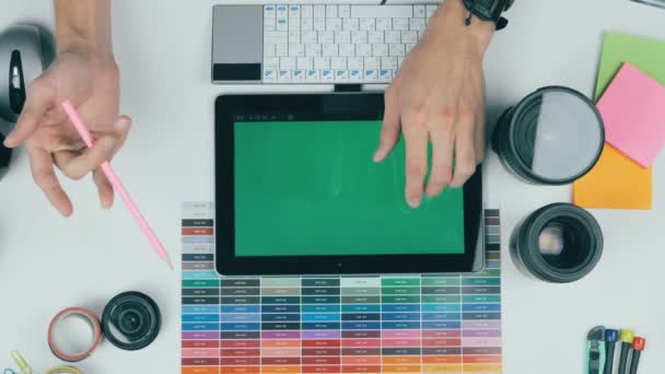 Top view. Man working on green screen tablet in a design studio. Creative background.