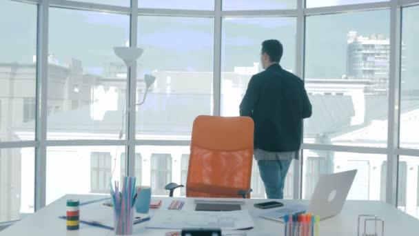 Professionellen Fotografen fotografieren mit Profi-Kamera in der Nähe von Panoramafenster im modernen Büro