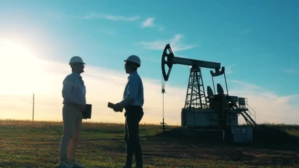 Two workers handshake agreement at oil field