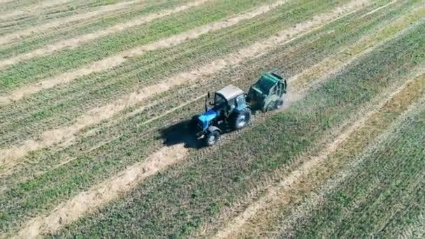 Traktor jede po poli a sbírá suchou trávu