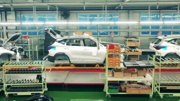 Boční pohled na bílá karoserie auta stojící na montážní lince. Automobilový průmysl, automobilová výrobní linka.