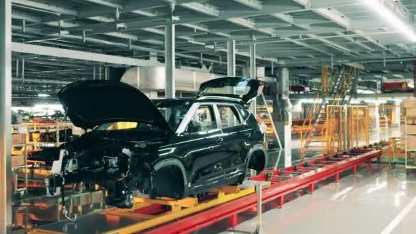 Fekete autó karosszériája halad a futószalagon. Autógyár belső tere.