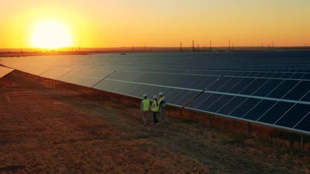 Három napenergia-specialista sétál át egy naperőműn fényes naplementekor.