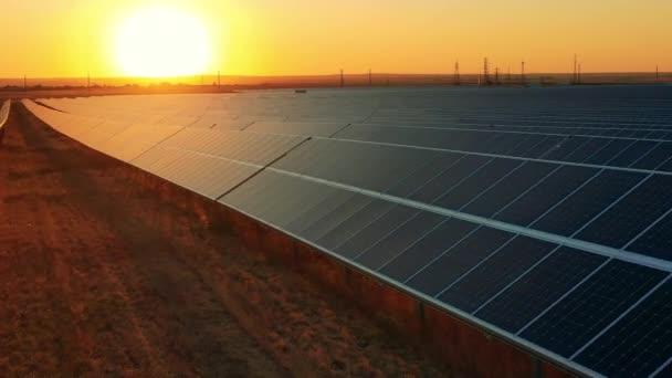Letecký pohled na masivní solární elektrárnu umístěnou na poli při jasném západu slunce