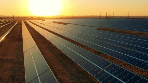 Pohled shora na obrovskou fotovoltaickou elektrárnu umístěnou na poli při západu slunce