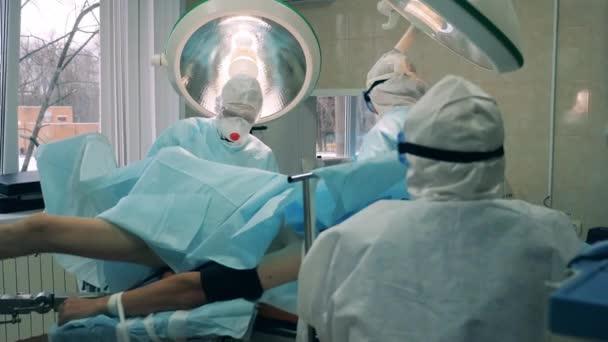 Chirurgen in Schutzanzügen operieren einen Patienten
