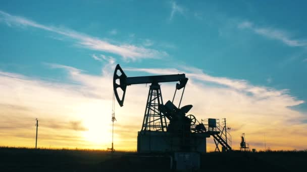 Silhouette of a working oil pumpjack in an oil field at sunset