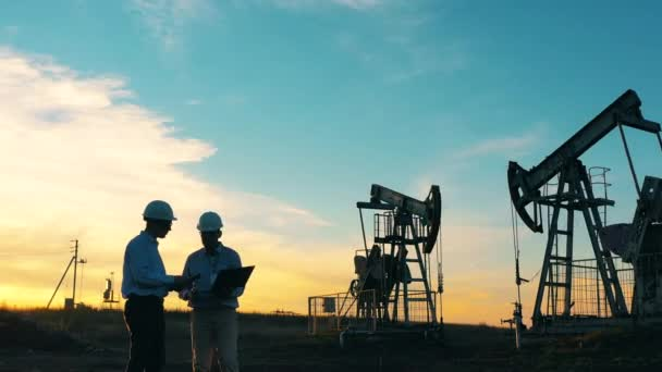Two oil industry workers inspecting an oil field with a laptop at sunset