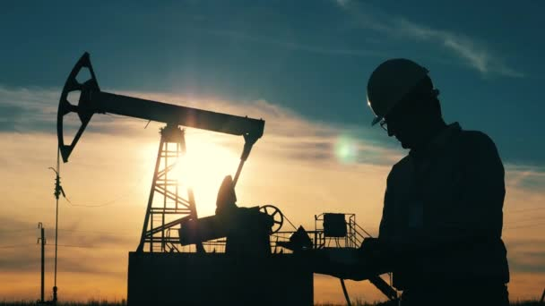 Silhouette of an oil industry worker with a laptop in an oil field