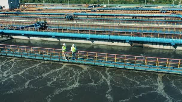 Zwei Abwasserbetreiber laufen an der Wasserreinigungsanlage entlang