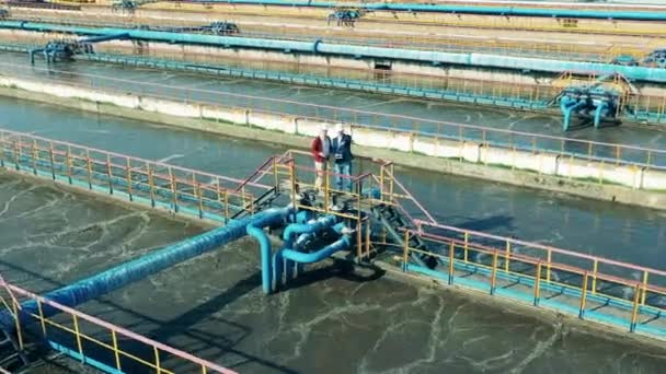 Zwei Fachleute diskutieren über eine große Abwasserreinigungsanlage