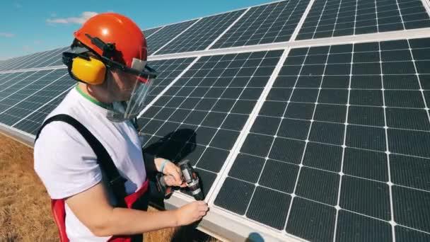 Napelemes technikus, aki napelemet állít össze egy naperőműben. Alternatív zöld energiával foglalkozó munkavállaló.
