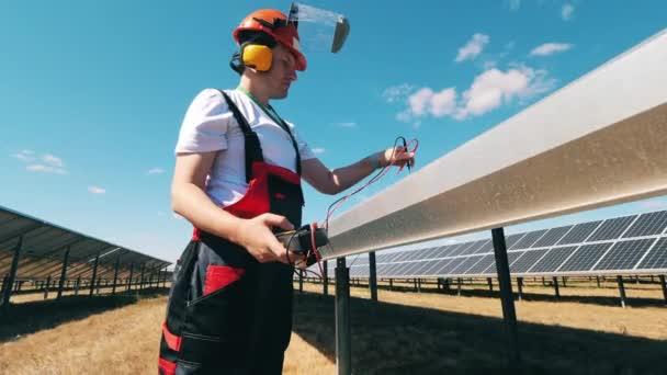 Napenergia-mérnök napelempaneleket tart fenn egy naperőműben egy speciális szerszámmal