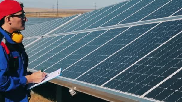 Napenergia-mérnök ellenőrzi a napelemeket egy naperőműben