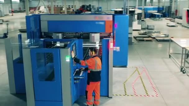 Pracovník chladírny provozuje průmyslový stroj. Pracovník pracující s průmyslovými zařízeními.