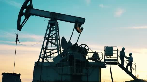 Two engineers talking near oil pumpjack at oil field