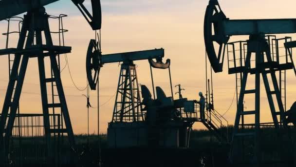 Engineer small figure among huge oil pumpjacks