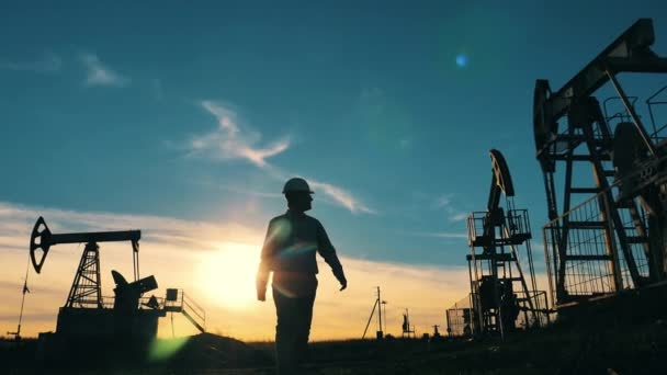 Engineer typing on laptop surrounded by oil pumpjacks at sunset
