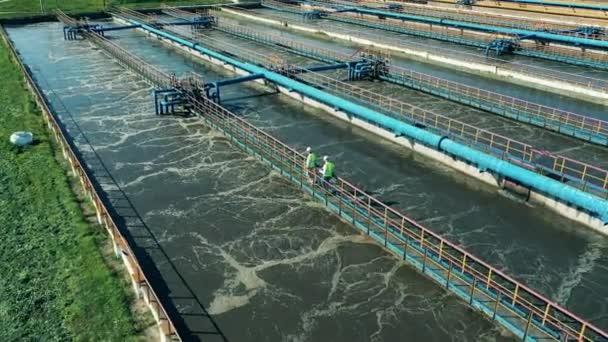 Zwei Abwasserbetreiber gehen an den Rohren einer Abwasserreinigungsanlage entlang. Abwasserkonzept.