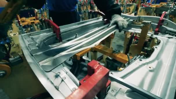 Pracovník automobilky umísťující díly automobilů na svařovací stroj