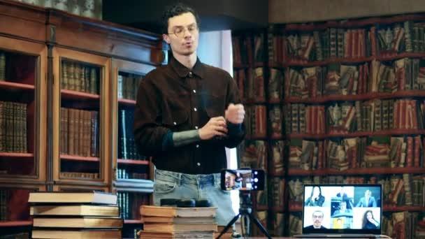 Männlicher Dozent leitet Online-Unterricht in einer Bibliothek