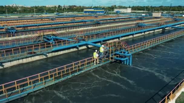 Abwasserbehandlung, Abwasserreinigungskonzept. Männliche Ingenieure laufen über die Abwasserreinigungsanlagen