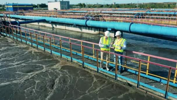 Männliche Ingenieure beobachten, wie Abwässer gereinigt werden. Abwasserbehandlung, Abwasserreinigungskonzept.