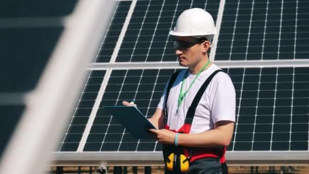 Wartungsspezialist macht sich neben Solarbatterien Notizen