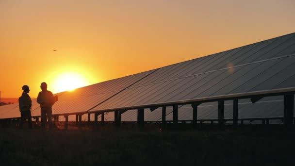 Dva bezpečnostní inspektoři procházejí kolem solárních baterií při západu slunce. Koncept elektřiny z obnovitelných zdrojů.