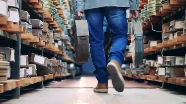 Ein Mann läuft mit Filmrollen in Koffern durch das Archiv