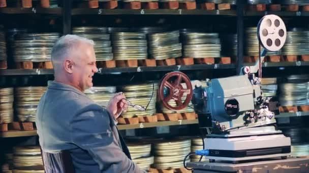 Vintage-Film, altes Kino-Konzept. Archivmitarbeiter lacht neben einem Oldtimer-Filmprojektor