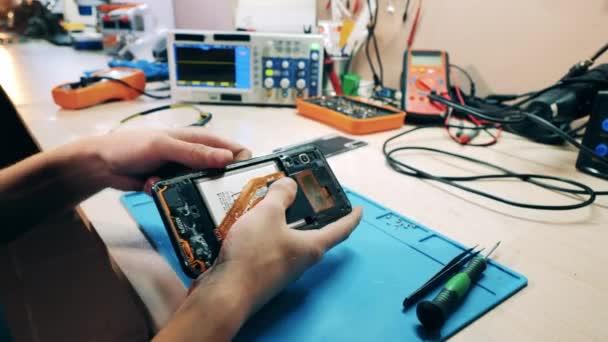 Reparateur demontiert ein Handy