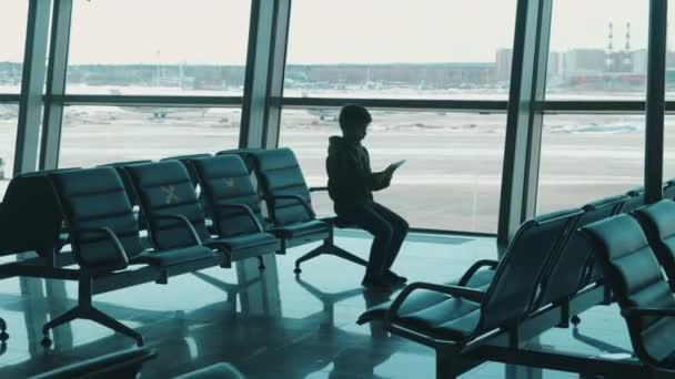 Chlapec používá tablet v prázdném odbavovacím salónku