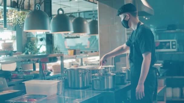 Muž kuchař v masce obličeje míchá vařící jídlo