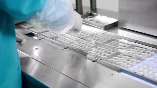 Fabrikarbeiter ersetzt einige Kapselpillen auf dem Förderband