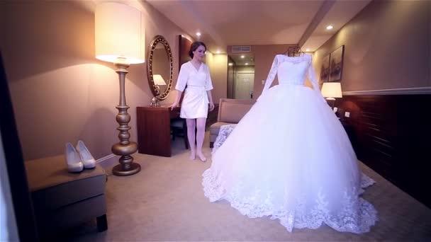 Nevěsta v blízkosti svatební šaty