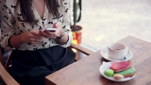 Junge schöne Frau mit Telefon sitzen in stilvollen café.