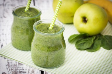 Green smoothie with apple,banana and spinach on a light background