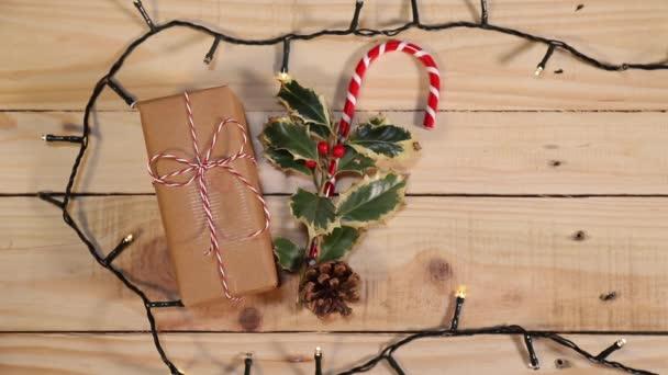 Vánoční doplňky pro dokonalého Santova pomocníka: listy cesmíny, cukrová třtina, zabalený dárek a měkká světla pro veselé a radostné Vánoce.