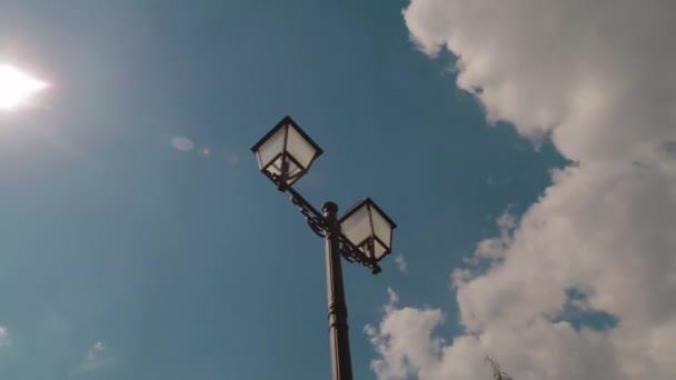 Straßenlaterne gegen den blauen Himmel mit weißen Wolken, Zeitraffer