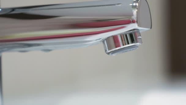 Goccia trasparente di acqua cade dal rubinetto