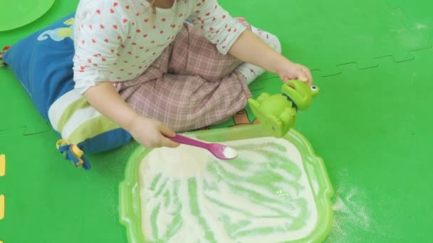 Dítě sedí na podlaze a hraje s hračkou
