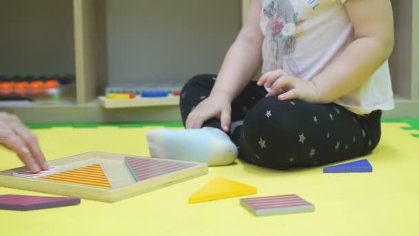 Dítě pracuje s hádanek sedí na podlaze