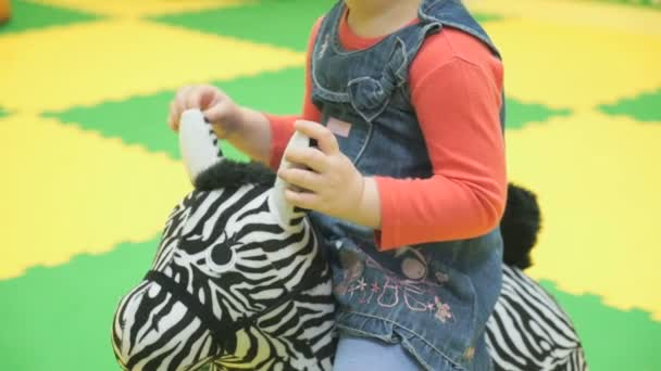 Child is ridden on a toy zebra